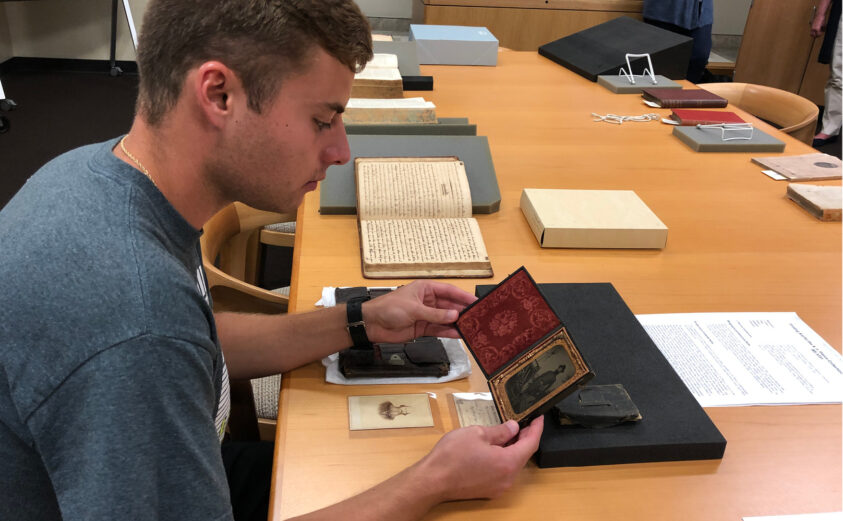 Student inspects framed photograph of Civil War soldier