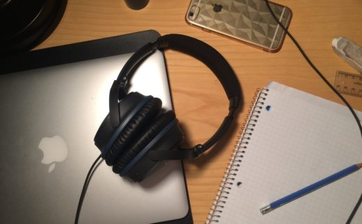 Photograph of notebook, headphones, tablet and cell phone on a desk