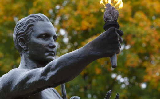 Torchbearer statue with fall leaves