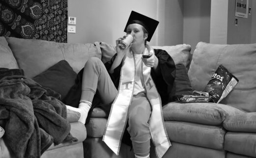 Image of a student on their couch, with their graduation attire on, enjoying a soda and holding their TV remote and snacks.