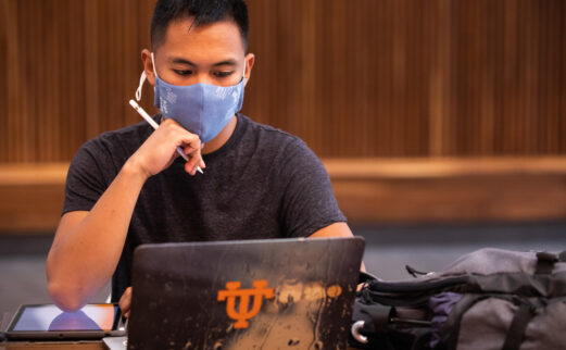 A masked student studies inside the Mossman Building at the start of the Fall Semester
