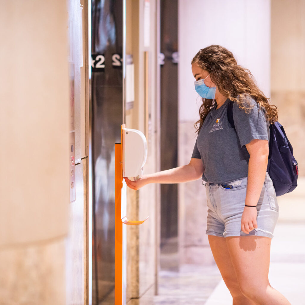 Student places hands under hand sanitizer dispenser for personal use