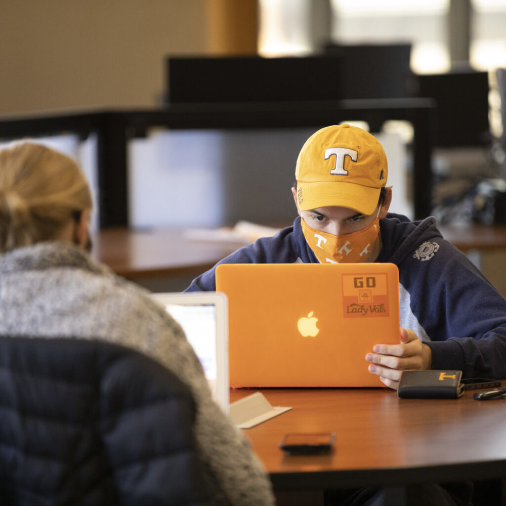 Student with a UT hat is using a laptop while seated at a desk in Hodges Library