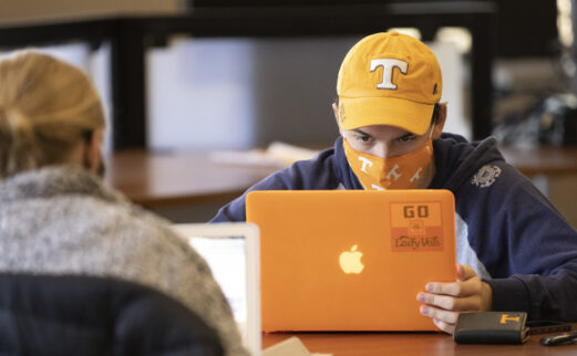 Student in a UT hat with laptop and mask studying in library