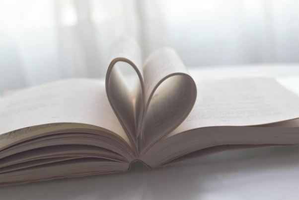 Image of book pages pulled together to form a heart