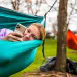 Student relaxes in a hammock while reading something on her cell phone screen.