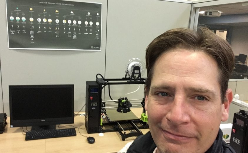 Image of IT technologist Richie Sexton, sitting in front of one of Pendergrass Library's 3D Printers