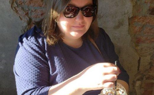 Image of Samantha Ward, wearing sunglasses and holding coffee