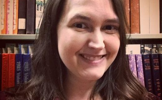 Image of Becky Briggs Becker in front of shelves of books