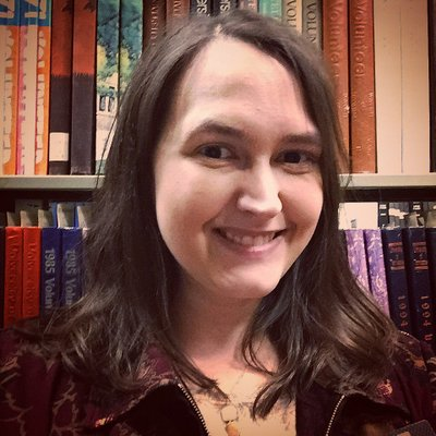 Photograph image of Becky Briggs Becker in front of book shelves