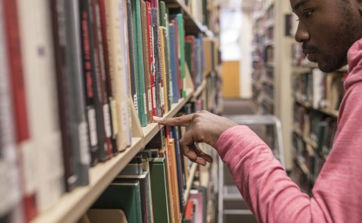 Student looking for books in John C. Hodges Library